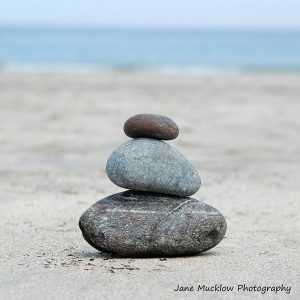 A tower of three pebbles on a beach, photo by Jane Mucklow Photography