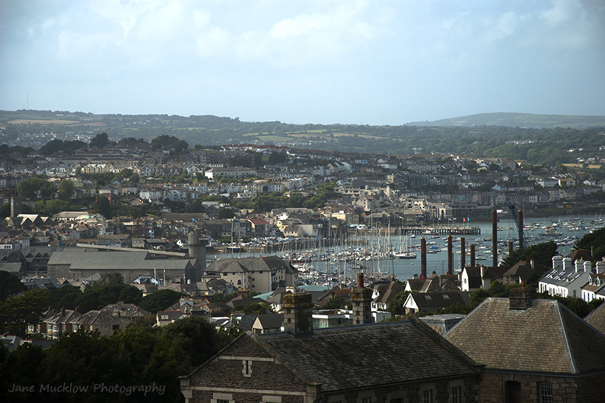 View across the roofs of Falmouth, river estuary and boats beyond, by Jane Mucklow Photography