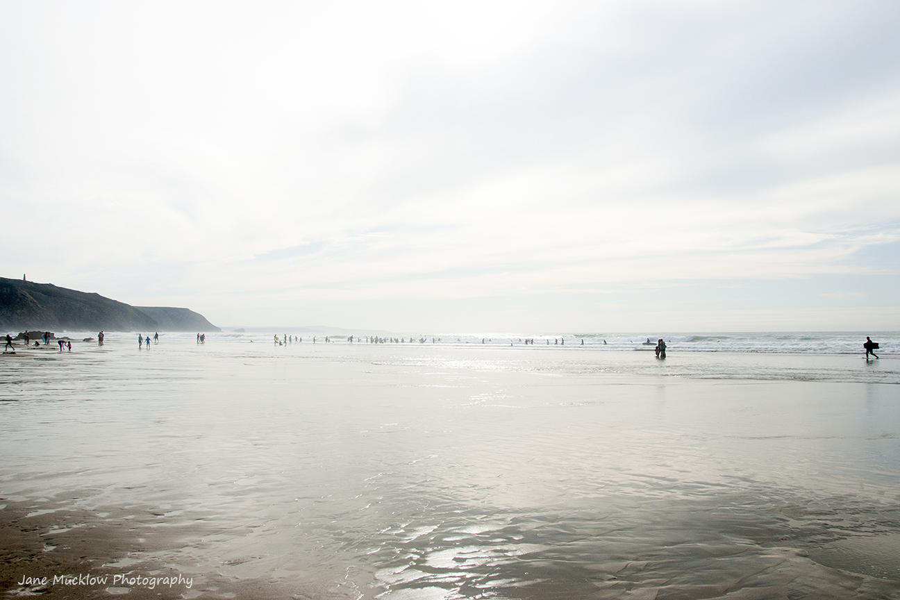 View across Porthtowan Beach, of the surfers at low tide by Jane Mucklow Photography