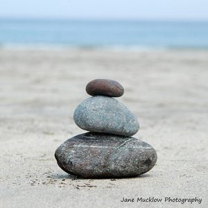 a pile of three grey pebbles on a beach, photo by Jane Mucklow Photography