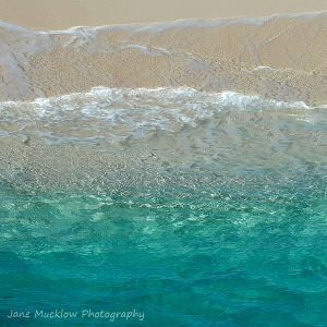 Photograph of a turquoise sea, waves gently lapping on the sand above, by Jane Mucklow Photography