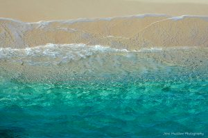 Photograph of a turquoise sea, gentle waves lapping on the sand, by Jane Mucklow
