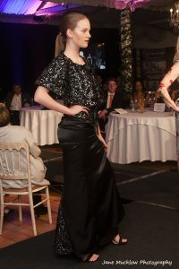 Photograph by Jane Mucklow of a model wearing a black two piece outfit with cape, designed by Caroline Bruce