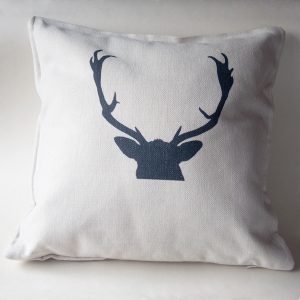 photo of a cream cushion printed in black with a stag's head, for sale by Jane Mucklow
