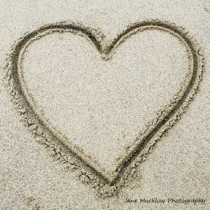 Photo of a heart drawn in some sand, by Jane Mucklow