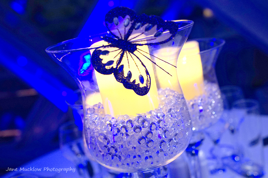 Photograph of a candle and butterfly table decoration by Jane Mucklow