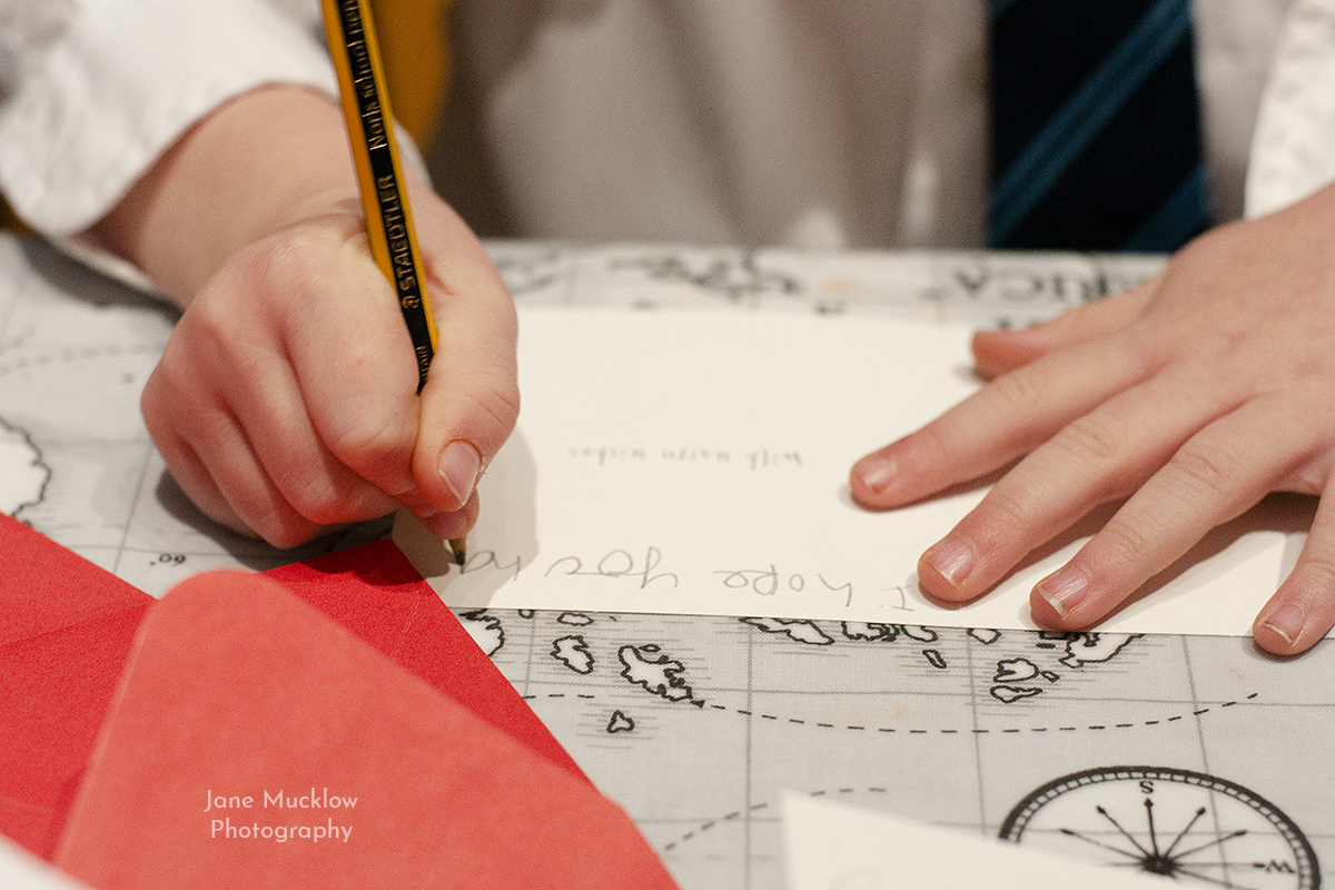 Photograph by Jane Mucklow, close up of child's hands writing a Christmas card