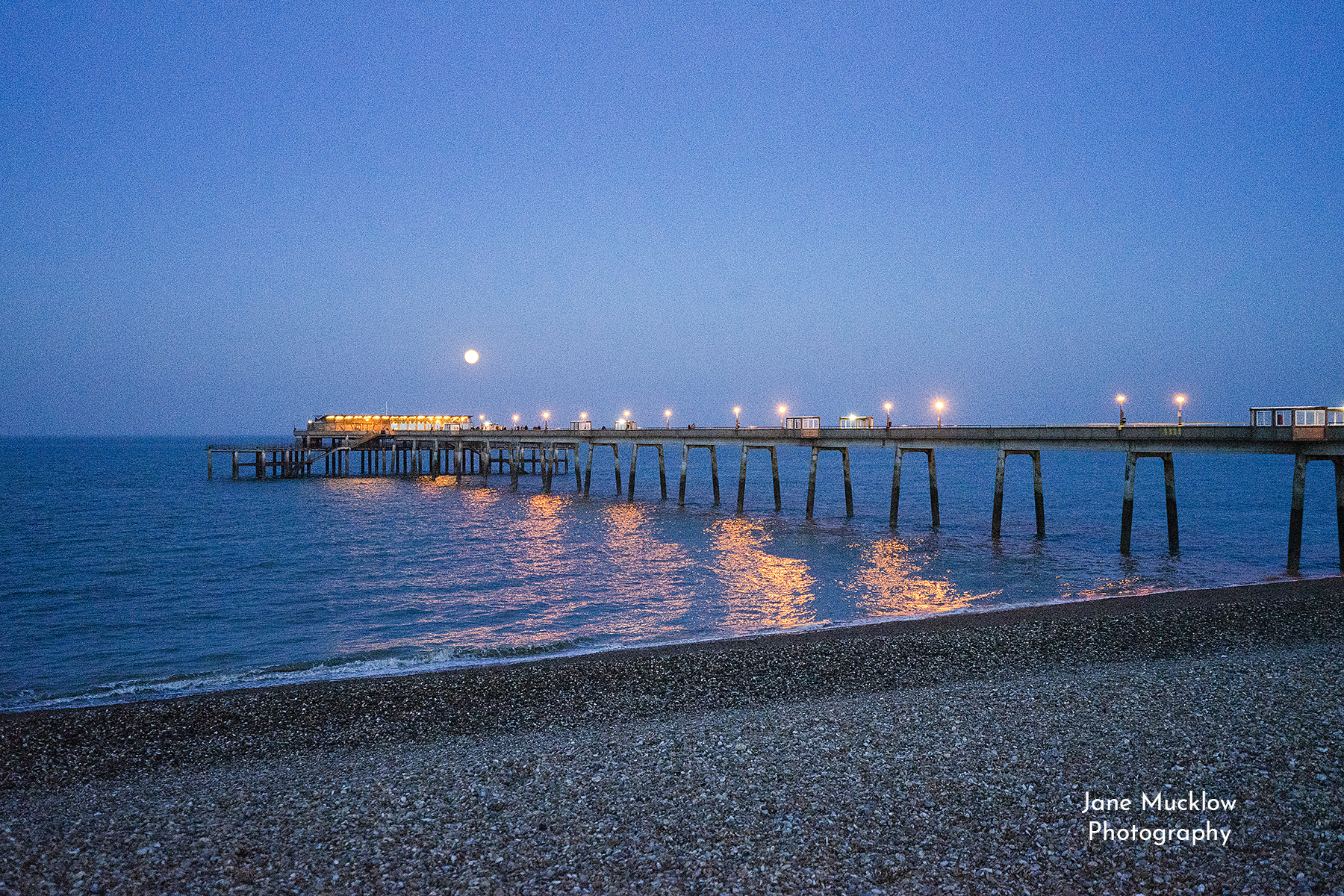 Photo by Jane Mucklow of a full moon rising over Deal Pier and the sea, just after sunset, Deal, Kent