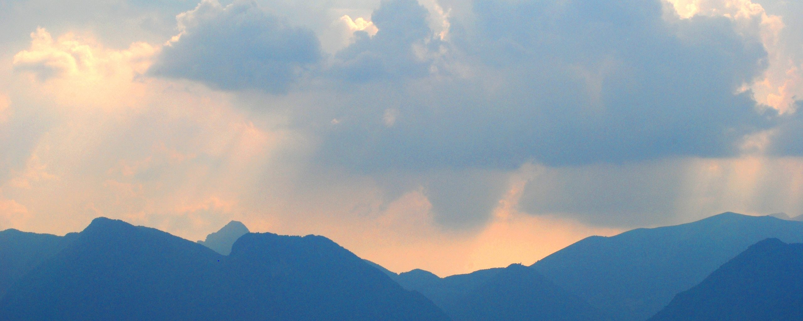 Photo by Jane Mucklow of a stormy sunset over Italian mountains, available as a canvas for your wall.
