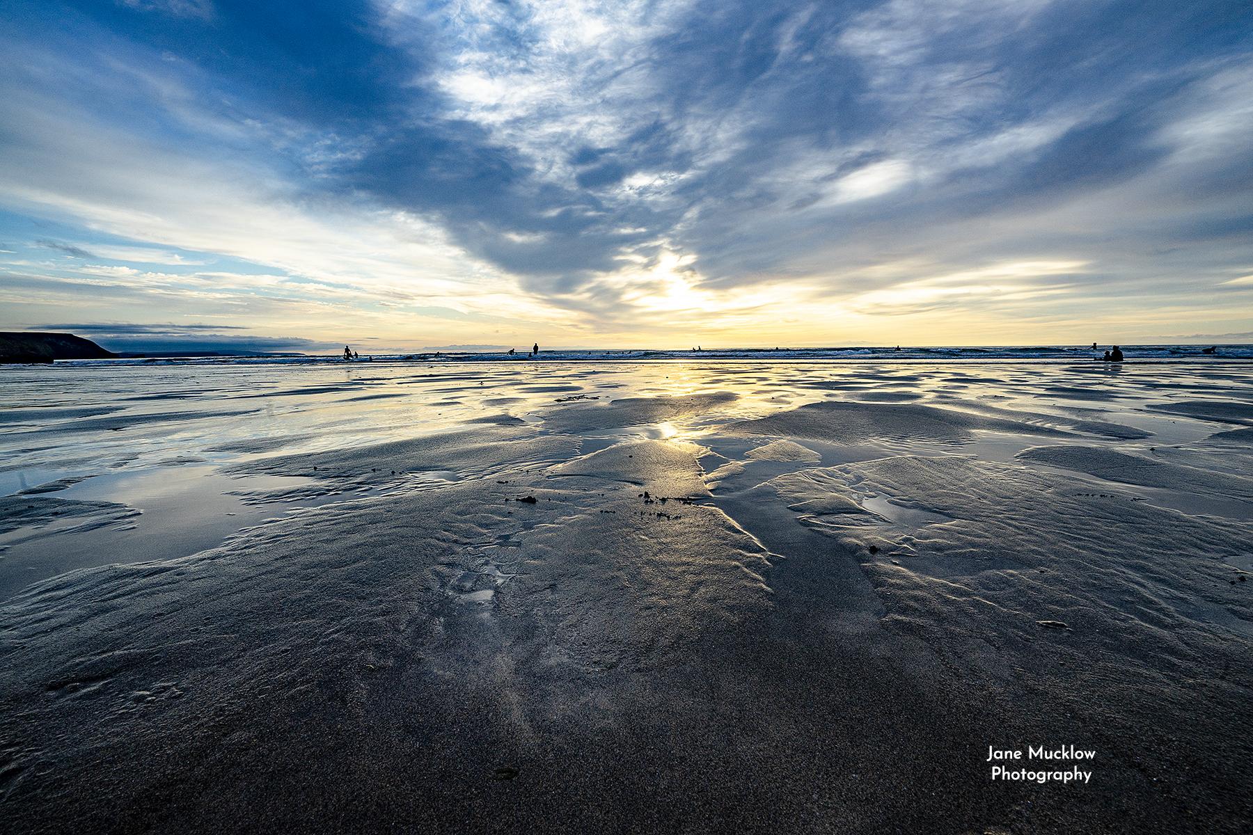 Photo of surfers at sunset Porthtowan Beach Cornwall by Jane Mucklow