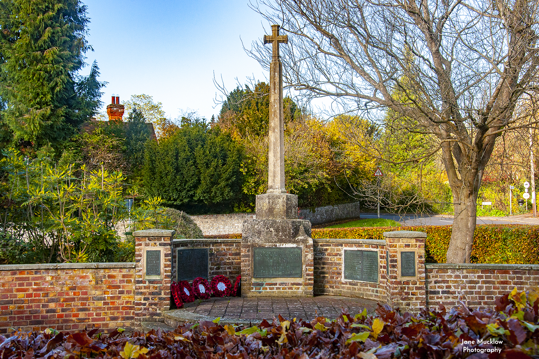 Photo of the war memorial in Kemsing, with Autumn leaves and poppy wreaths, by Jane Mucklow