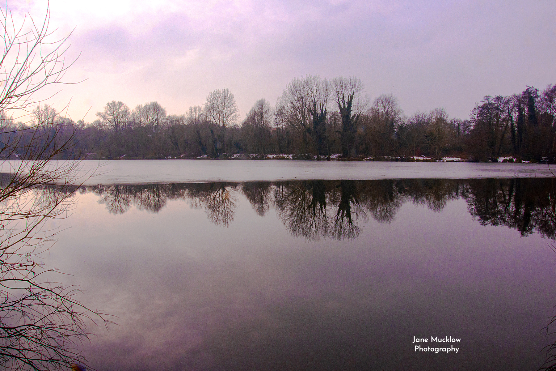 Photo of a winter sunset and reflections on an icy lake at Sevenoaks Wildlife Reserve, by Jane Mucklow